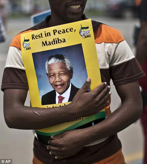 Figurehead: A South African mourner embraces a poster of Mandela, while waiting with other mourners for the motorcade transporting the body of the former president to pass by in the town of Mthatha. Right, Khanyile Diko cheers while wearing a T-shirt depicting the liberation hero as a scarf around his neck