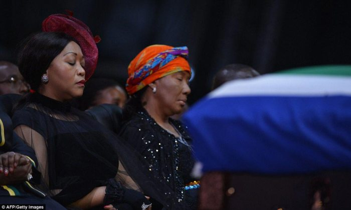 Moved: Mandela's daughter Makaziwe, centre, sits in front of her father's coffin during the ceremony