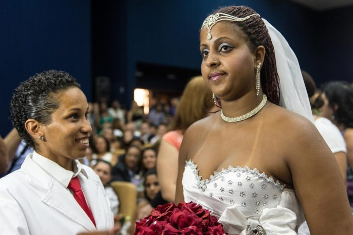 Gabrielle Costa (R) and Joyce Xavier gesture during their wedding ceremony at the Court of Justice of the State of Rio de Janeiro in Rio de Janeiro, Brazil, on December 8, 2013. 130 gay couples are getting married in the first massive wedding ceremony since the first gay marriage in Rio de Janeiro in 2011. AFP PHOTO / YASUYOSHI CHIBA (Photo credit should read YASUYOSHI CHIBA/AFP/Getty Images)