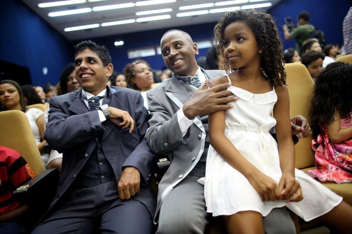 Couple Marcel (R) and Geraldo sit with their daughter Kevellen, 8, before marrying at what was billed as the world's largest communal gay wedding on December 8, 2013 in Rio de Janeiro, Brazil. 130 couples were married at the event which was held at the Court of Justice in downtown Rio. In May, Brazil became the third country in Latin America to effectively approve same-sex marriage via a court ruling, but a final law has yet to be passed. (Photo by Mario Tama/Getty Images)