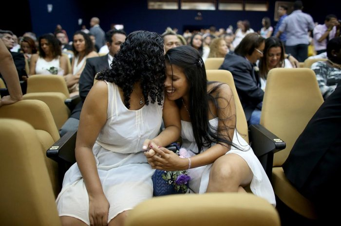 Couple Ingrid (L) and Tamires embrace before marrying at what was billed as the world's largest communal gay wedding on December 8, 2013 in Rio de Janeiro, Brazil. 130 couples were married at the event which was held at the Court of Justice in downtown Rio. In May, Brazil became the third country in Latin America to effectively approve same-sex marriage via a court ruling, but a final law has yet to be passed. (Photo by Mario Tama/Getty Images)
