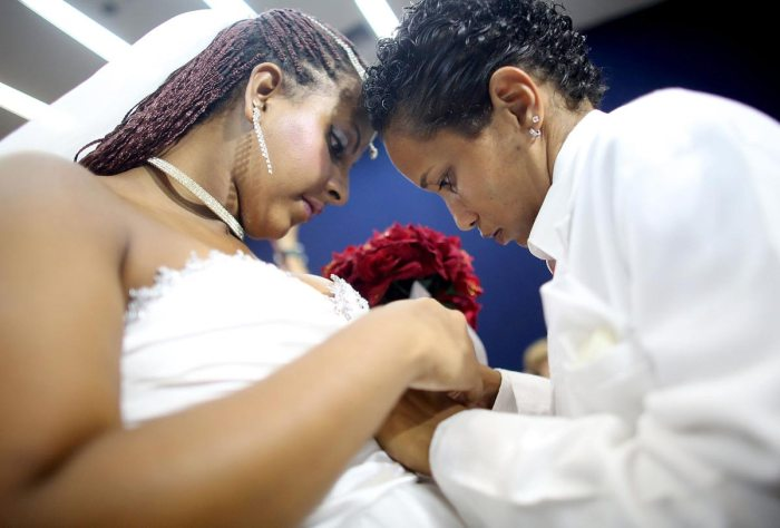 Joyce and Gabrieli (L) make an adjustment before marrying at what was billed as the world's largest communal gay wedding on December 8, 2013 in Rio de Janeiro, Brazil. 130 couples were married at the event which was held at the Court of Justice in downtown Rio. In May, Brazil became the third country in Latin America to effectively approve same-sex marriage via a court ruling, but a final law has yet to be passed. (Photo by Mario Tama/Getty Images)