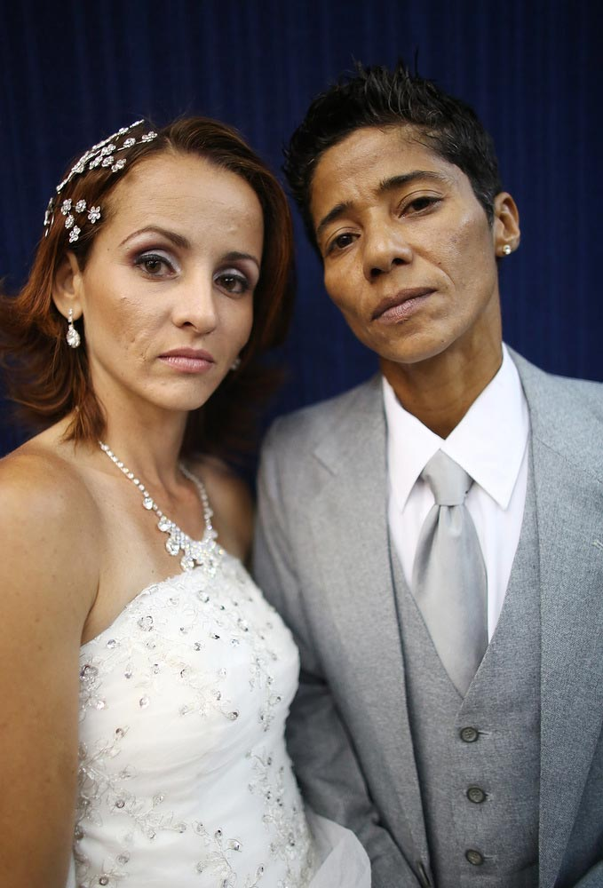 Couple Emmanuela and Romilda (R) pose before marrying at what was billed as the world's largest communal gay wedding on December 8, 2013 in Rio de Janeiro, Brazil. 130 couples were married at the event which was held at the Court of Justice in downtown Rio. In May, Brazil became the third country in Latin America to effectively approve same-sex marriage via a court ruling, but a final law has yet to be passed. (Photo by Mario Tama/Getty Images)