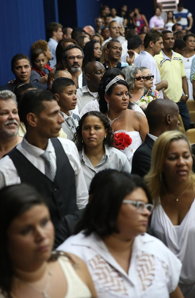 Newly married couples line up to be photographed on stage at what was billed as the world's largest communal gay wedding on December 8, 2013 in Rio de Janeiro, Brazil. 130 couples were married at the event which was held at the Court of Justice in downtown Rio. In May, Brazil became the third country in Latin America to effectively approve same-sex marriage via a court ruling, but a final law has yet to be passed. (Photo by Mario Tama/Getty Images)