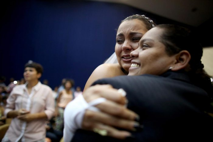 Newly married couple Ana Paula and Juliana (R) react at what was billed as the world's largest communal gay wedding on December 8, 2013 in Rio de Janeiro, Brazil. 130 couples were married at the event which was held at the Court of Justice in downtown Rio. In May, Brazil became the third country in Latin America to effectively approve same-sex marriage via a court ruling, but a final law has yet to be passed. (Photo by Mario Tama/Getty Images)