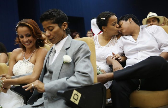 A couple kisses before getting married at what was billed as the world's largest communal gay wedding on December 8, 2013 in Rio de Janeiro, Brazil. 130 couples were married at the event which was held at the Court of Justice in downtown Rio. In May, Brazil became the third country in Latin America to effectively approve same-sex marriage via a court ruling, but a final law has yet to be passed. (Photo by Mario Tama/Getty Images)