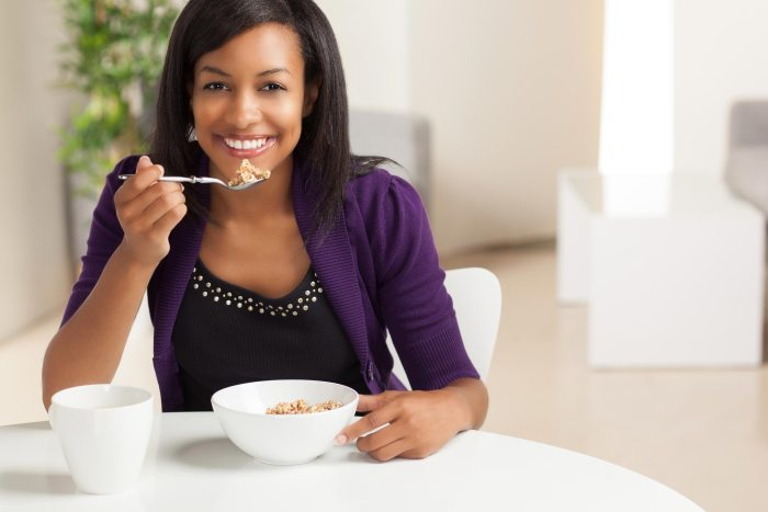 Attractive African American eating breakfast