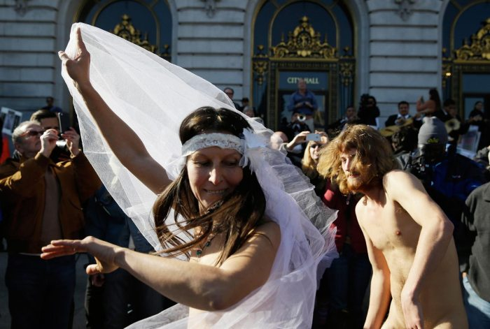 Gypsy Taub, left, dances with Jaymz Smith, right, following their nude wedding outside City Hall Thursday, Dec. 19, 2013, in San Francisco. Taub, the face and body of San Francisco's nude rights movement, tied the knot outside City Hall and was later cited and released by police. Taub, a mother of three who conducts nude interviews on public access TV, has been arrested repeatedly for violating the city's public nudity ban. (AP Photo/Eric Risberg)