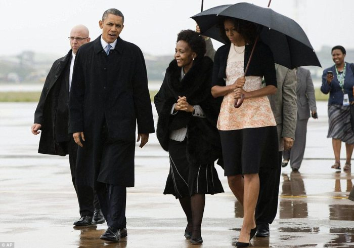 Welcoming committee: President Obama and Michelle (who is covered by an umbrella) are greeted Tuesday morning on the tarmac in Johannesburg by International Relations Minister Maite Nkoane-Mashabane (center)