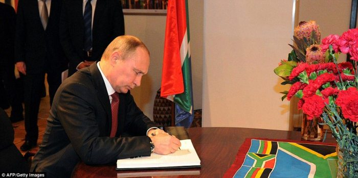 Not attending: Russia's president Vladimir Putin today signed a book of condolence for Mandela's death at the South African embassy in Moscow