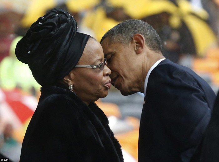Giving his condolences: President Obama kisses Nelson Mandela's widow Graca Machel during the memorial service