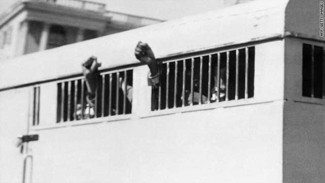 Mandela's anti-apartheid activities made him a frequent target of South Africa's authorities. He was sentenced to life imprisonment in June 1964 and spent nearly 27 years incarcerated, jailed on charges of treason and sabotage -- but fundamentally for his anti-apartheid actions. Here, eight men, including Mandela, leave the Palace of Justice in Pretoria on June 1964 with their fists raised in defiance through the barred windows of the prison car.