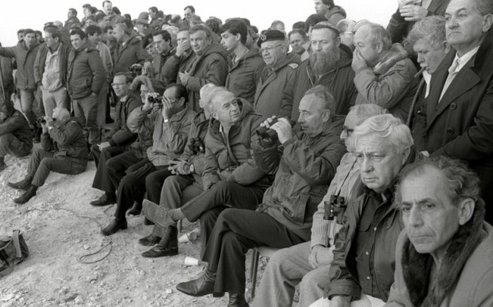 Shimon Peres (4th R) and the then Israeli Industry and Trade Minister Ariel Sharon (2nd R) and Israeli Army officials watch the final stage of a large scale military manoeuvre in December 1985 (Picture: Reuters)