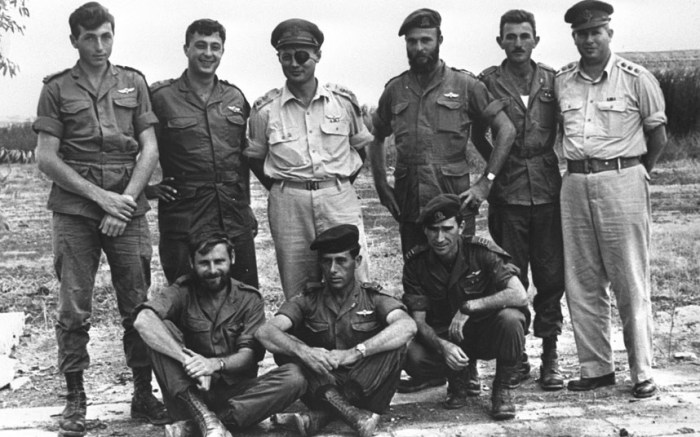 In this 1955 handout from the Israeli Governmental Press Office, Ariel Sharon poses as a young paratroop officer (2nd L) with Chief of Staff Moshe Dayan (3rd L and other officers posing after an attack on the Kunteila police station in the Sinai Desert (Picture: Ministry of Defense via Getty Images)