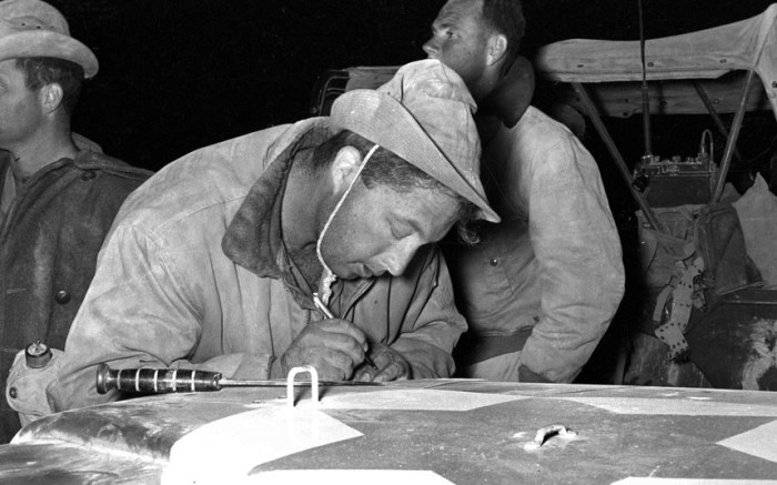 Israeli army officer Ariel Sharon writes a note on the hood of a jeep before a military manoeuvre on the Mitla Pass during the 1956 Operation Kadesh in the Sinai Desert in Egypt (Picture: Ministry of Defense via Getty Images)