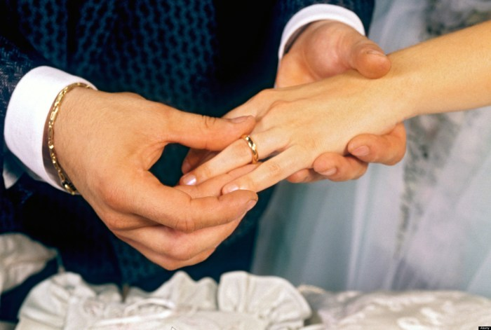 Groom places gold wedding ring on the finger of his new bride in marriage ceremony