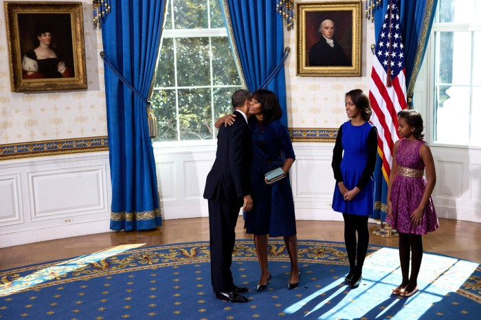 U.S President Barack Obama (L) hugs the first lady Michelle Obama (2nd L) as daughters Malia (C) and Sasha look on after taking the oath of office in the Blue Room of the White House January 20, 2013 in Washington, DC. Obama and U.S. Vice President Joe Biden were officially sworn in a day before the ceremonial inaugural swearing-in.  (Photo Credit: Doug Mills-Pool/Getty Images)
