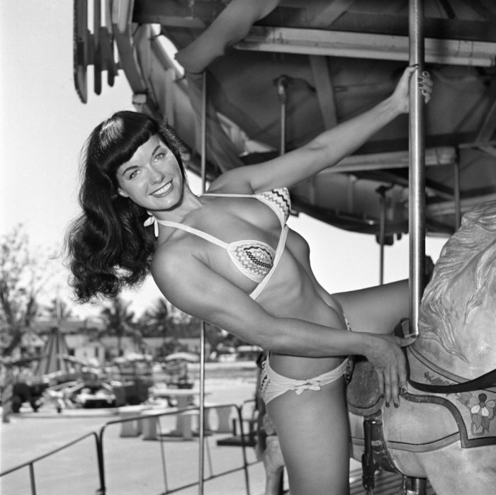 In this photo taken in 1954 by photographer Bunny Yeager, model Bettie Page poses on a merry-go-round at an amusement park in Miami. Yeager was a model who become a pin-up photographer in the 50's and 60's. (Photo Credit: AP/Copyright Bunny Yeager)