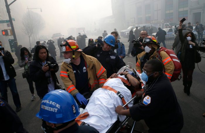 A victim is removed by emergency personnel near an apparent building explosion fire and collapse in New York City on March 12, 2014. (Mike Segar—Reuters)