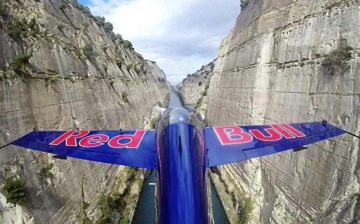 Red Bull pilot Peter Besenyei navigates his way down the Corinth Canal in Greece in his plane (Photo Credit: RED BULL)