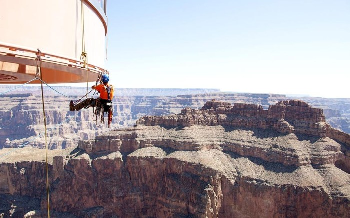 A technician from Abseilon USA works to clean more than 40 panes of glass underneath the horseshoe-shaped bridge on the Grand Canyon Skywalk in Arizona (Photo Credit: REUTERS)