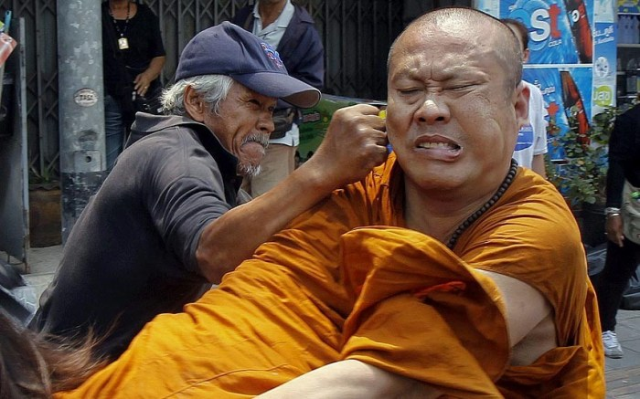 Members of the pro-government 'red shirt' movement attack a Buddhist monk outside the National Anti-Corruption Commission office in Nonthaburi province, Thailand. Members of the movement attacked the monk after he complained to the group as they blocked a road near the National Anti-Corruption Commission. (Photo Credit: CHAIWAT SUBPRASOM/REUTERS)
