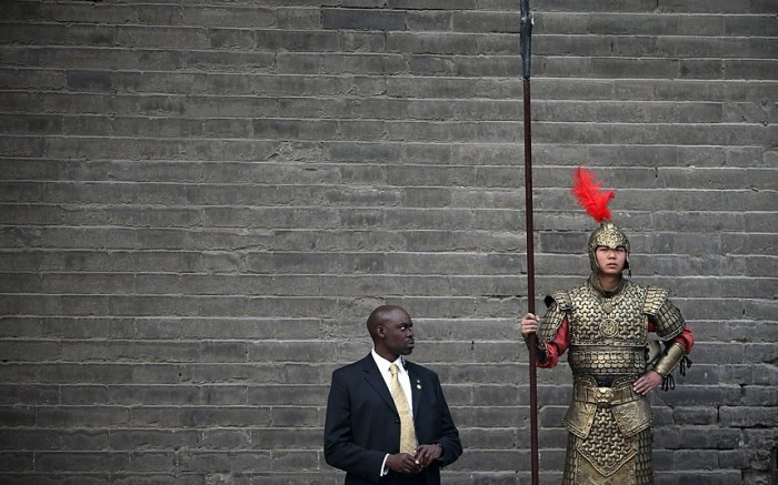 One of U.S. first lady Michelle Obama's security detail eyes a man in Chinese ancient warrior costume during Obama's visit at the City Wall in Xi'an, China (Photo Credit:  GETTY IMAGES)