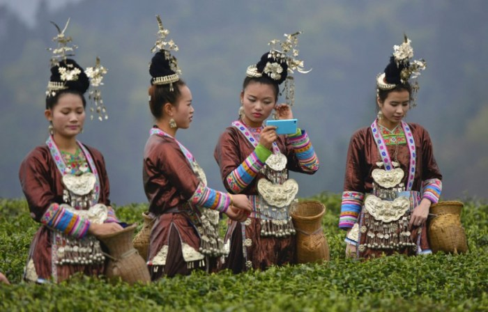 Ethnic Dong women wearing traditional costumes pick tea leaves during a ceremony marking the start of tea picking season in spring, at a tea plantation in Liping county, Guizhou province. According to local media, Liping county's tea plantations attracted more than 60,000 women workers from nearby villages this spring and each tea picker earns around 100 yuan ($16.10) per diem. (Photo Credit:  REUTERS/Sheng Li)