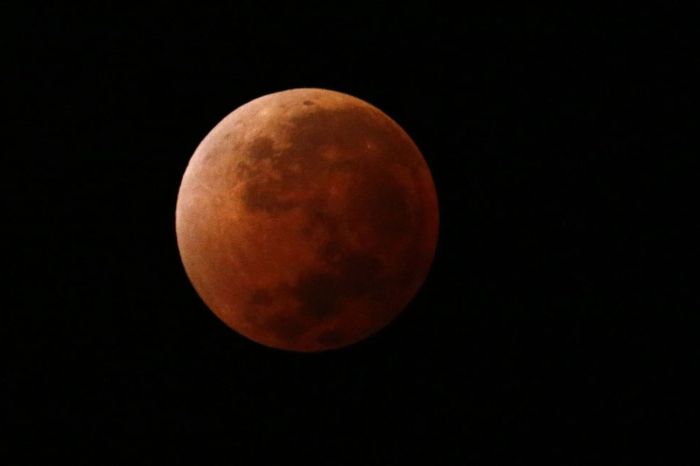 The moon is seen as it begins a total lunar eclipse that will turn the moon red (Photo Credit: Getty Images)