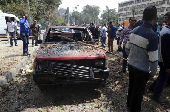 People stand near a damaged car after explosions near Cairo University April 2, 2014. | Photo: Reuters