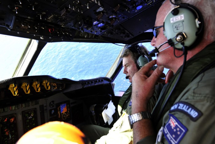 Royal New Zealand Air Force (RNZAF) Co Pilot squadron Leader Brett McKenzie (L) and Flight Engineer Trent Wyatt sit in the cockpit aboard a P3 Orion maritime search aircraft as it flies over the southern Indian Ocean looking for debris from missing Malaysian Airlines flight MH370 on April 11, 2014. (Photo Credit: Richard Polden - Pool/Getty Images)