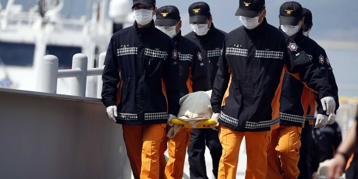 Officials carry away a body of the victim of the ferry disaster