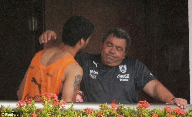Goodbyes: Luis Suarez is seen embracing a member of the coaching staff on a balcony at the team hotel (Photo Credit: AP)