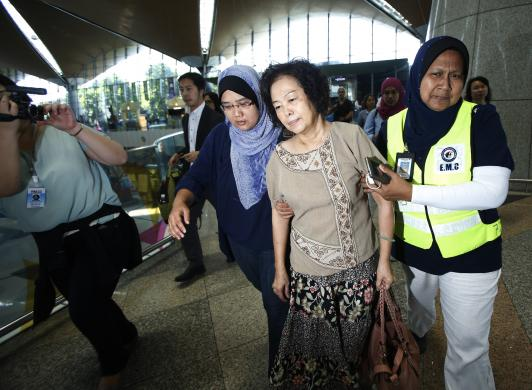 The Malaysian relative of a passenger onboard the Malaysia Airlines (MAS) MH17 is assisted by MAS staff members as she leaves Kuala Lumpur International Airport in Sepang July 18, 2014.  [Photo Credit: REUTERS/Edgar Su]