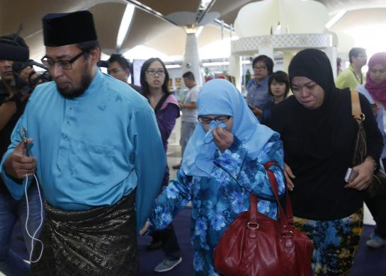 Relatives of passengers onboard the downed Malaysia Airlines flight MH-17 arrive at Kuala Lumpur International Airport in Sepang July 18, 2014. [Photo Credit:  REUTERS/Olivia Harris]