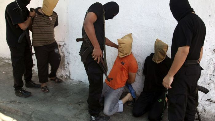 Hamas militants grab Palestinians suspected of collaborating with Israel, before executing them in Gaza City. [photo credit: Reuters]