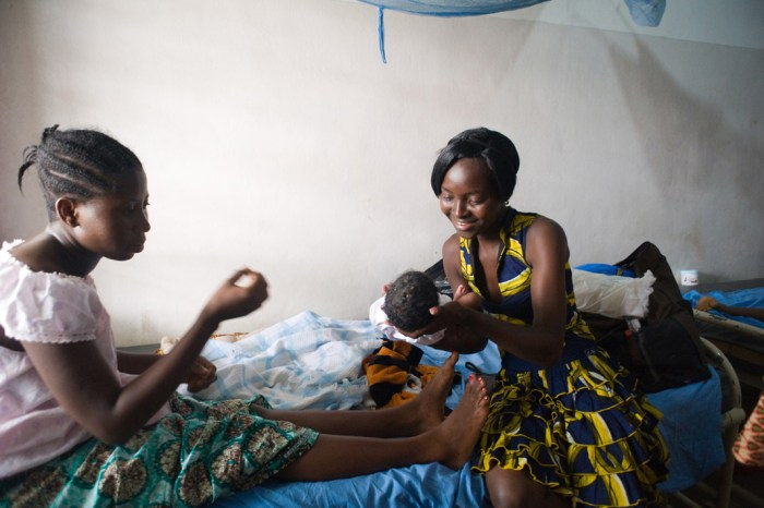 A visitor holds Habibat Adeboye's baby shortly after delivery at the Doctors Without Borders-run Aiyetoro Health Centre in Lagos, Nigeria. The clinic offers free care to women who live in a slum and have poor access to health care. At the time, federal doctors were on strike. (Photo Credit: Alice Proujansky)