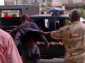 An Officer Dragging One of The Kidnappers Into the Van