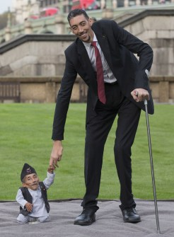 Chandra Bahadur Dangi, from Nepal, (L) the shortest adult to have ever been verified by Guinness World Records, is pictured with the world's tallest man Sultan Kosen from Turkey, during a photocall in London on November 13, 2014, to mark Guinness World Records Day. Chandra Dangi, measures a tiny 21.5in (0.54m) the same height as six stacked cans of beans. Sultan Kosen measures 8 ft 3in (2.51m). (Photo Credit: Andrew Cowie/AFP/Getty Images)
