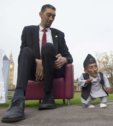 Chandra Bahadur Dangi, from Nepal, (R) the shortest adult to have ever been verified by Guinness World Records, poses for pictures with the world's tallest man Sultan Kosen from Turkey, during a photocall in London on November 13, 2014, to mark Guinness World Records Day. Chandra Dangi, measures a tiny 21.5in (0.54m) the same height as six stacked cans of beans. Sultan Kosen measures 8 ft 3in (2.51m). (Photo Credit: Andrew Cowie/AFP/Getty Images)