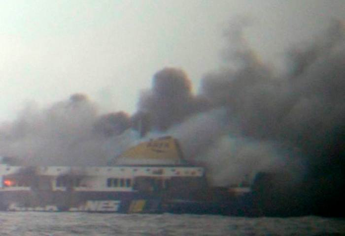 In this photo taken from a nearby ship, smoke rises from the Italian-flagged Norman Atlantic ferry after it caught fire in the Adriatic Sea, Sunday, Dec. 28, 2014. The ferry carrying some hundreds of passengers caught fire off the Greek island of Corfu early Sunday, trapping passengers on the top decks as gale-force winds and choppy seas hampered their evacuation. (Photo Credit: AP/SKAI TV Station)