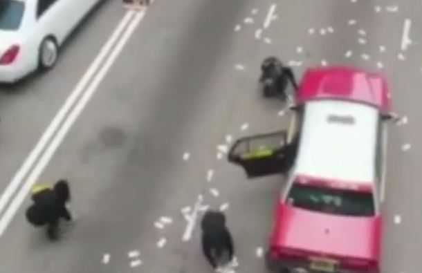 Crowd Gathered In The Middle Of The Road To Pick Money In Hong Kong (Photo Credit: Metro UK)