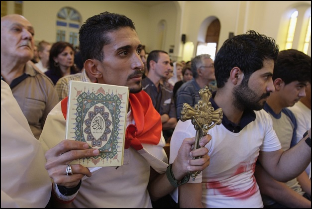 An Iraqi man holding a cross and al-qur'an during mass at Mar Girgis Church in Baghdad (Photo Credit: Reuters/IBT)