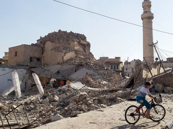 A boy bikes past the Prophet Jirjis mosque in Mosul, Iraq, on July 27, 2014. The Muslim shrine was destroyed by militants who overran the city in June. (Photo Credit: AP)