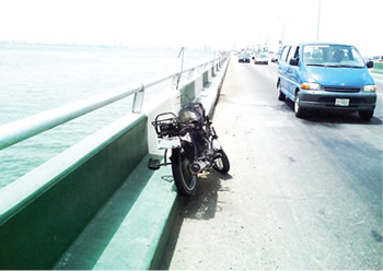 The charred remains of the motorcycle which went up in flames after it tumbled burning one policeman and leaving the other with severe injuries at Third Mainland Bridge, Lagos state on Tuesday, March 24, 2015. (Photo Credit: Punch)
