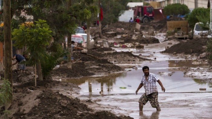 A man tried to cross a flooded road in Chile (Photo Credit:CNN)