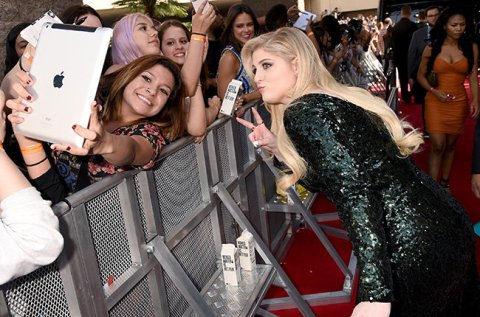 Meghan Trainor poses for selfie with a fan (Credit: Invision/AP)