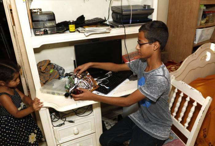 Ahmed Mohamed at home working on his clock which got him arrested in school.