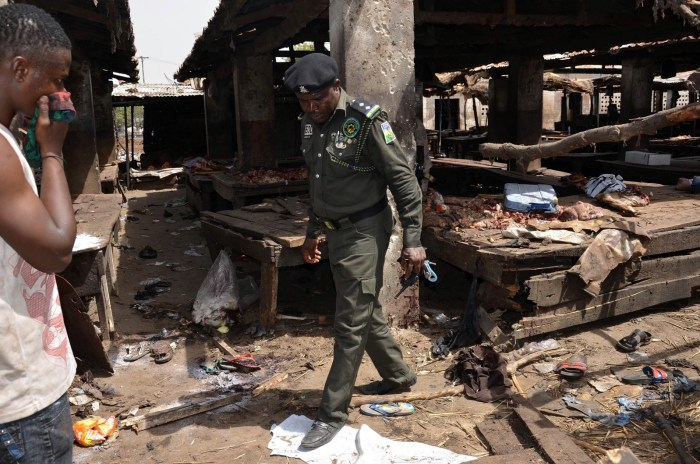 A Nigerian policeman inspects the site of a suicide attack at a busy cattle market in the northeastern Nigerian city of Maiduguri on June 2, 2015.   AFP/Stringer