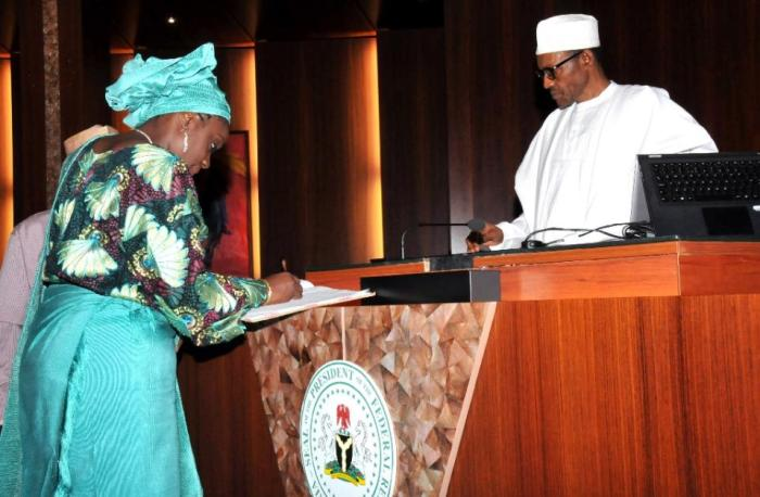 Newly appointed Finance Minister, Kemi Adeosun signs the register before President Muhammadu Buhari in Abuja on November 11, 2015 | AFP